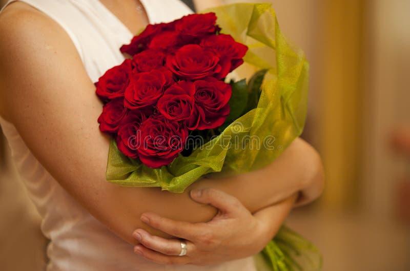 Mazzo delle rose rosse o cremisi in mani della donna immagini stock