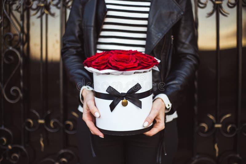 Mazzo delle rose rosse in una scatola nelle mani di una ragazza fotografie stock libere da diritti