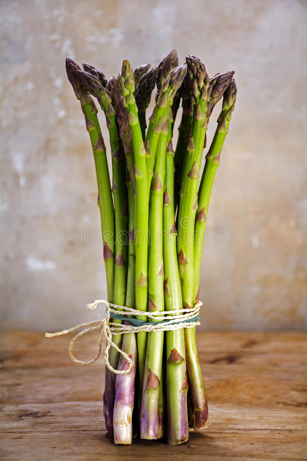 Mazzo di asparago verde fresco che sta su una tavola di legno rustica fotografia stock libera da diritti