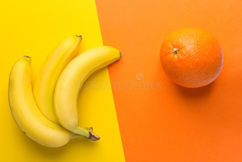 Mazzo di banane mature gialle arancio su fondo bitonale Disposizione piana d'avanguardia creativa Cibo pulito dell'alimento sano fotografie stock