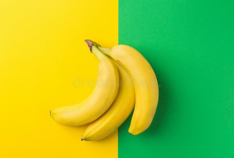 Mazzo di banane mature su fondo verde giallo bitonale Disposizione piana d'avanguardia creativa Cibo pulito dell'alimento sano fotografia stock