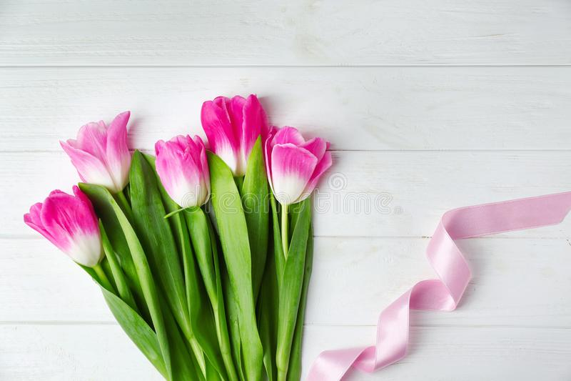 Mazzo di bei tulipani con il nastro di colore su fondo di legno bianco, vista superiore immagini stock libere da diritti
