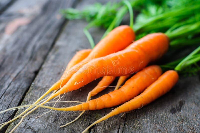 Mazzo di carota lavata fresca sui vecchi precedenti di legno fotografie stock libere da diritti