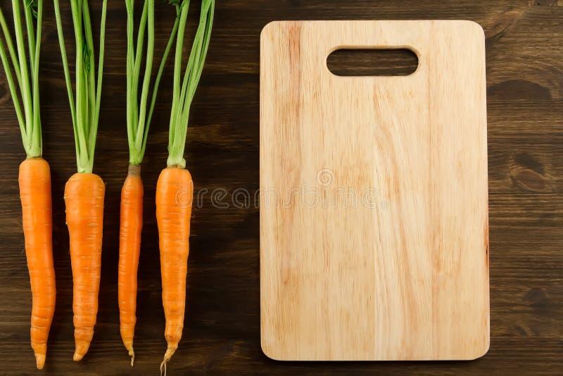 Mazzo di carote fresche con le foglie verdi ed il tagliere immagini stock libere da diritti