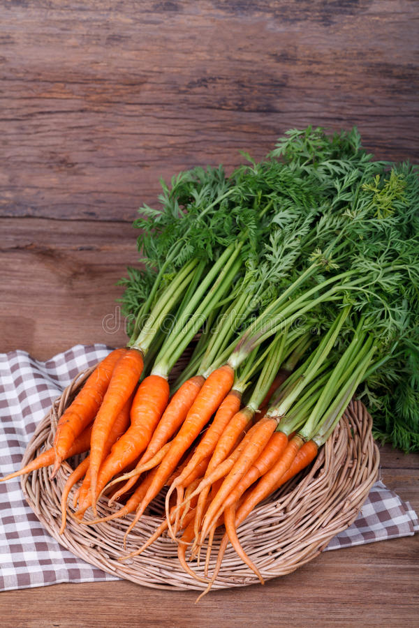 Mazzo di carote fresche con le foglie verdi sopra fondo di legno fotografie stock