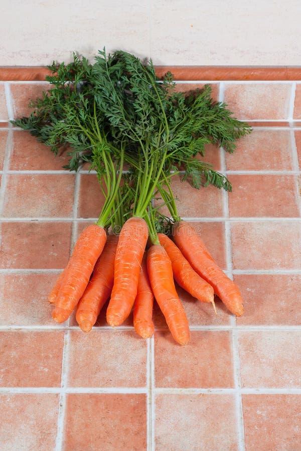 Mazzo di carote nella cucina, su un fondo delle mattonelle immagine stock