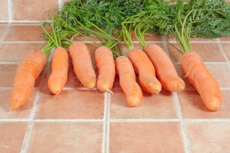 Mazzo di carote nella cucina, su un fondo delle mattonelle fotografie stock