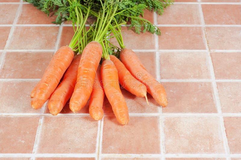 Mazzo di carote nella cucina, su un fondo delle mattonelle immagini stock libere da diritti
