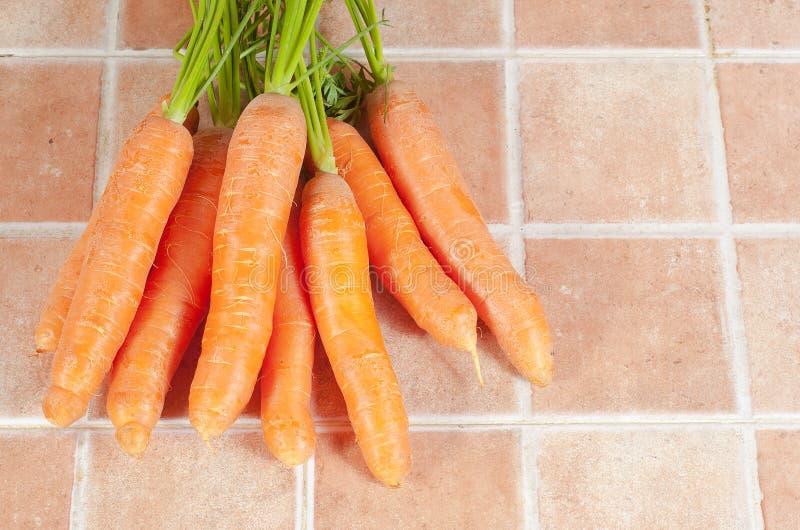 Mazzo di carote nella cucina, su un fondo delle mattonelle fotografie stock libere da diritti