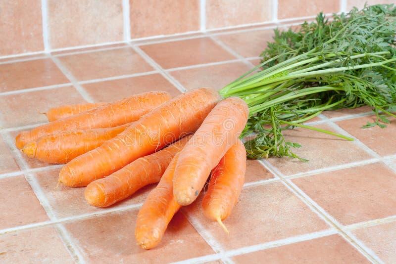 Mazzo di carote nella cucina, su un fondo delle mattonelle fotografia stock libera da diritti