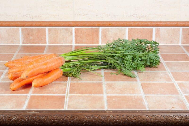 Mazzo di carote nella cucina, su un fondo delle mattonelle fotografia stock