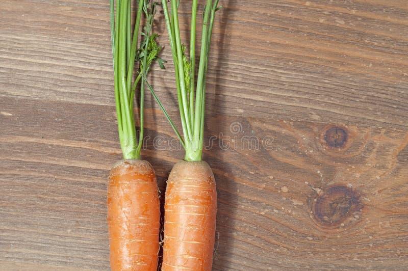 Mazzo di carote nella cucina, su un fondo di legno della tavola immagine stock