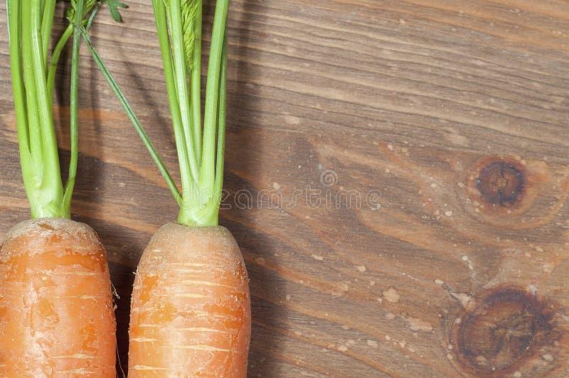 Mazzo di carote nella cucina, su un fondo di legno della tavola immagini stock libere da diritti