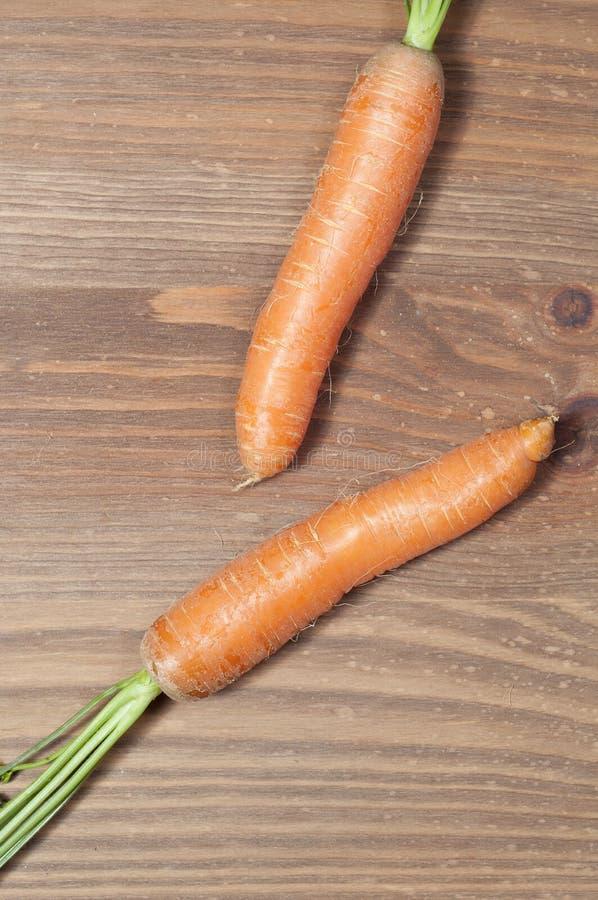 Mazzo di carote nella cucina, su un fondo di legno della tavola immagine stock libera da diritti