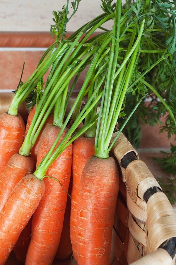 Mazzo di carote su un canestro, su un fondo delle mattonelle immagine stock libera da diritti