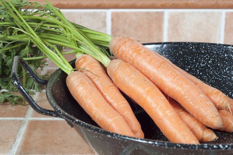 Mazzo di carote su una ciotola, su un fondo delle mattonelle immagine stock