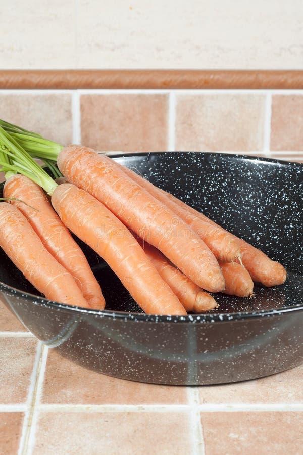 Mazzo di carote su una ciotola, su un fondo delle mattonelle fotografia stock