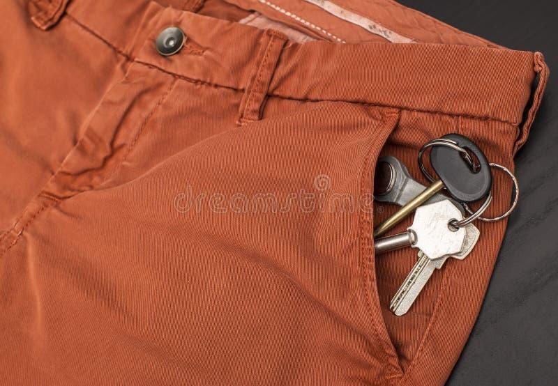 Mazzo di chiavi che attaccano dalla sua tasca del pantalone che sono sulla tavola fotografia stock libera da diritti
