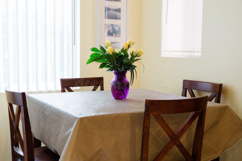 Mazzo di compleanno di rose gialle in un vaso porpora su una tavola della sala da pranzo immagini stock libere da diritti