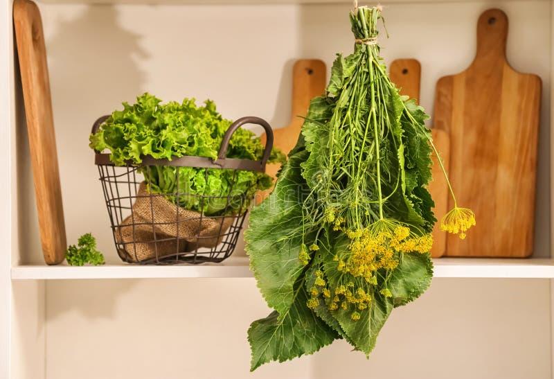 Mazzo di complesso di erbe vicino al canestro con lattuga fresca sullo scaffale immagine stock