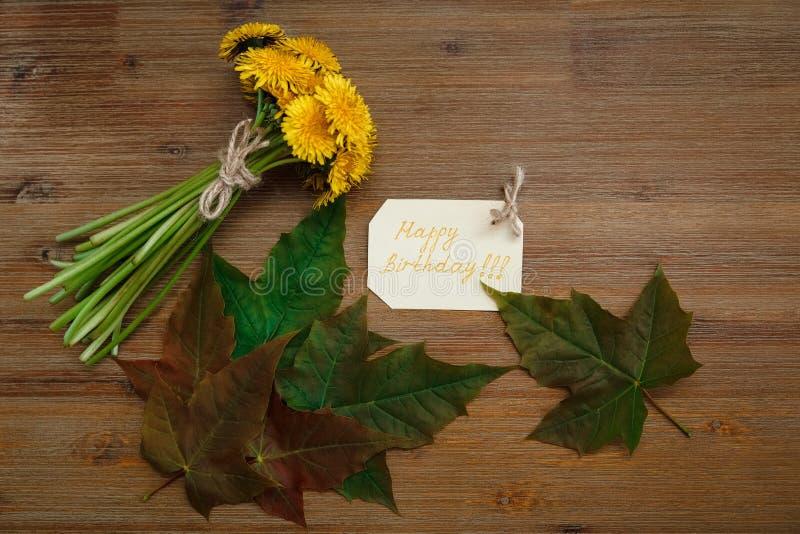Mazzo di denti di leone gialli, carta di desiderio di compleanno, foglie verdi Il fondo di Autumn Garden Tabella di legno fotografie stock libere da diritti
