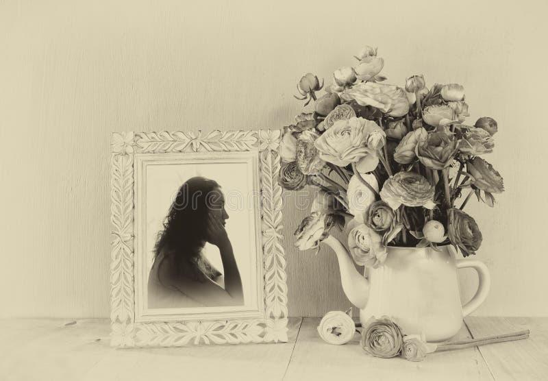 Mazzo di estate dei fiori e del telaio vittoriano con il ritratto d'annata della giovane donna sulla tavola di legno imag in bian immagini stock