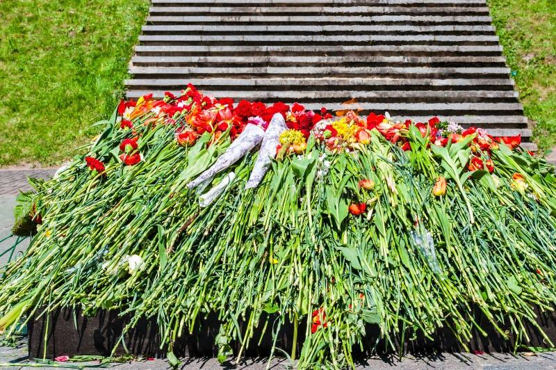 Mazzo di fiori che indicano vicino al monumento eterno della fiamma sul cimitero militare in onore del giorno della vittoria nell fotografia stock