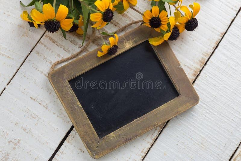 Mazzo di fiori gialli luminosi e di lavagna vuota fotografie stock libere da diritti