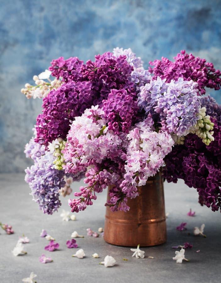 Mazzo di fiori lilla in una brocca dell'annata del bottaio Spazio blu della copia del fondo fotografie stock