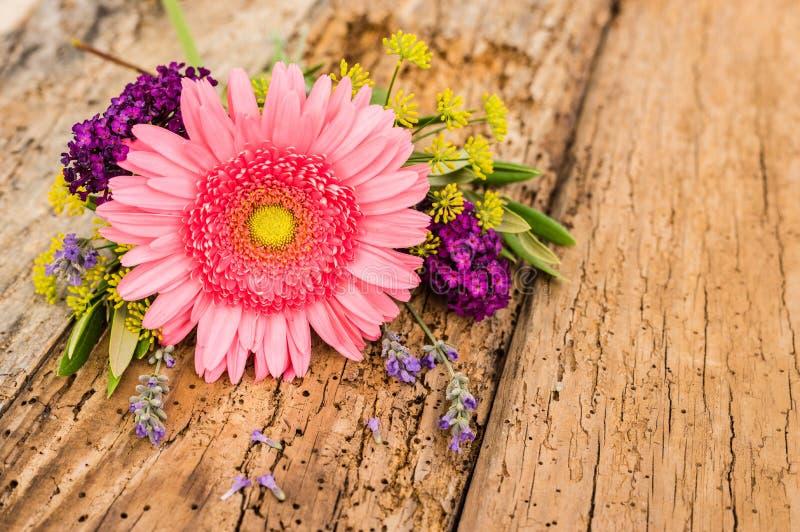 Mazzo di fiori romantico con la margherita rosa della gerbera su fondo di legno rustico con lo spazio della copia immagini stock