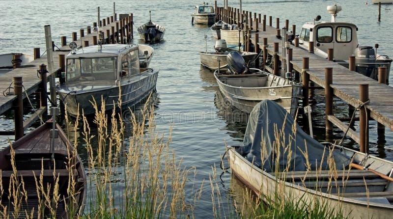 Mazzo di Grey Motorboat sul bacino di legno di Brown fotografia stock libera da diritti