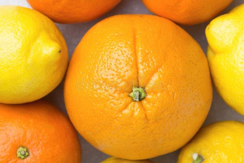 Mazzo di interi limoni succosi maturi dei mandarini delle arance degli agrumi sulla Tabella di marmo di pietra bianca Disintossic fotografia stock libera da diritti
