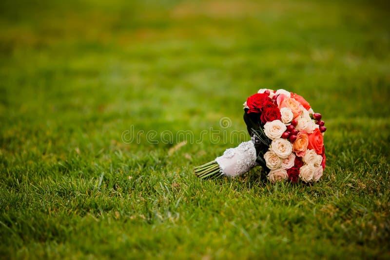 Mazzo di nozze della sposa all'erba verde immagine stock libera da diritti