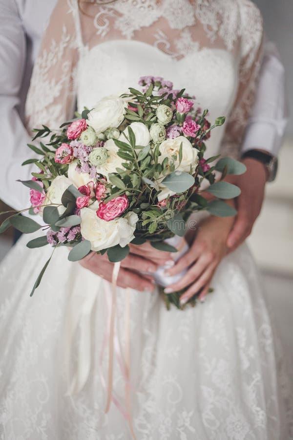 Mazzo di nozze della tenuta dello sposo e della sposa immagine stock libera da diritti