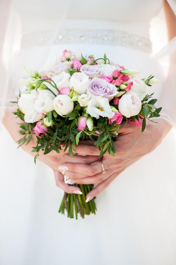 Mazzo di nozze in mani del ` s della sposa fotografie stock libere da diritti