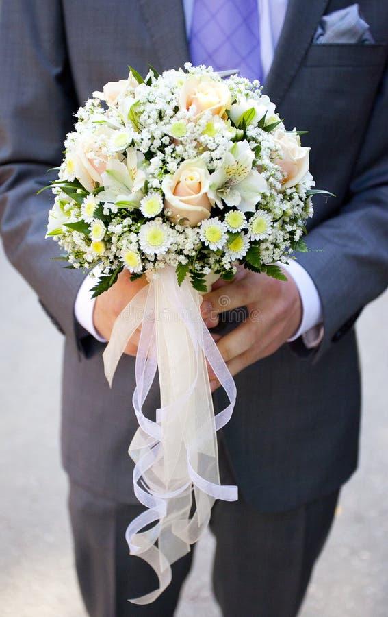 Mazzo di nozze di pallido - fiori e nastri rosa e gialli in mani dello sposo fotografia stock libera da diritti