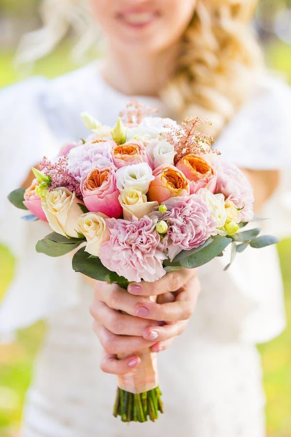 Mazzo di nozze di pallido - rose rosa e bianche in mani della sposa fotografia stock