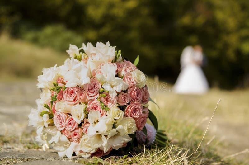 Mazzo di nozze sull'erba e sulle persone appena sposate fotografia stock