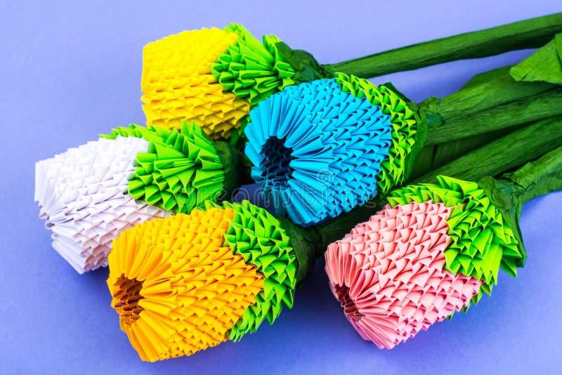 Mazzo di origami dei fiori multicolori su fondo viola fotografie stock libere da diritti