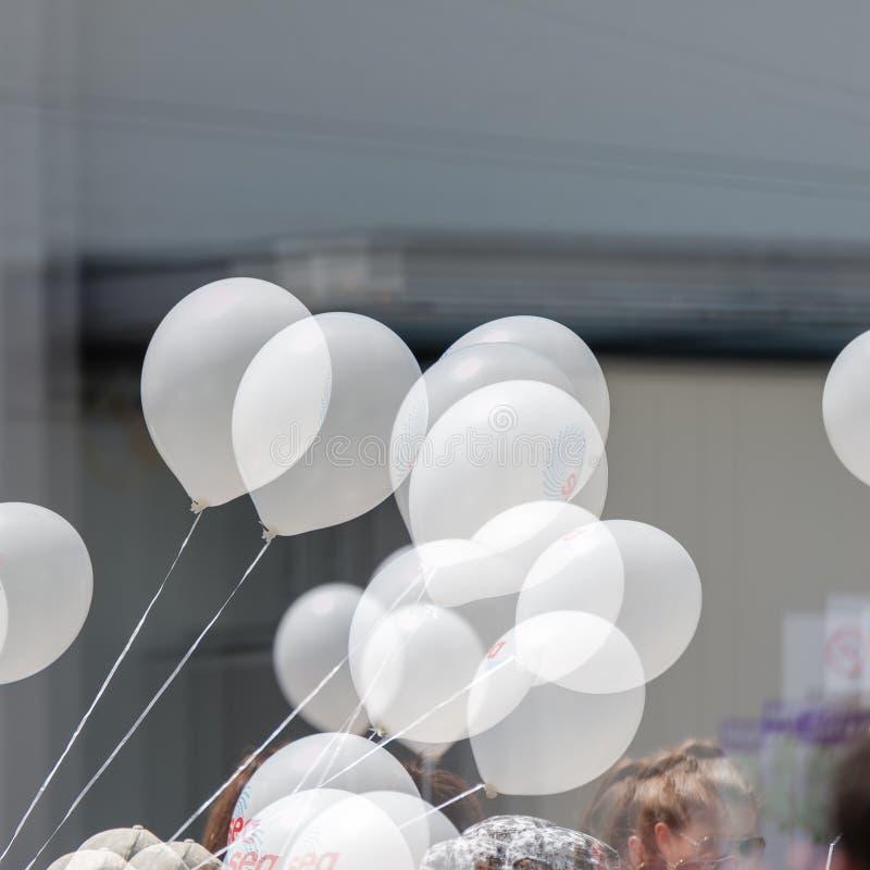 Mazzo di palloni bianchi dell'elio sulle corde ad un evento all'aperto, con doppia esposizione immagine stock
