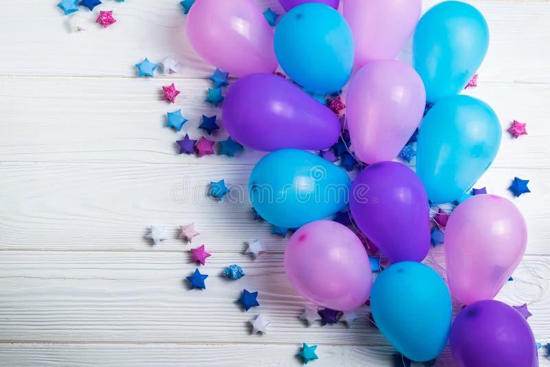 Mazzo di palloni variopinti del partito con le stelle di carta su fondo di legno bianco immagini stock