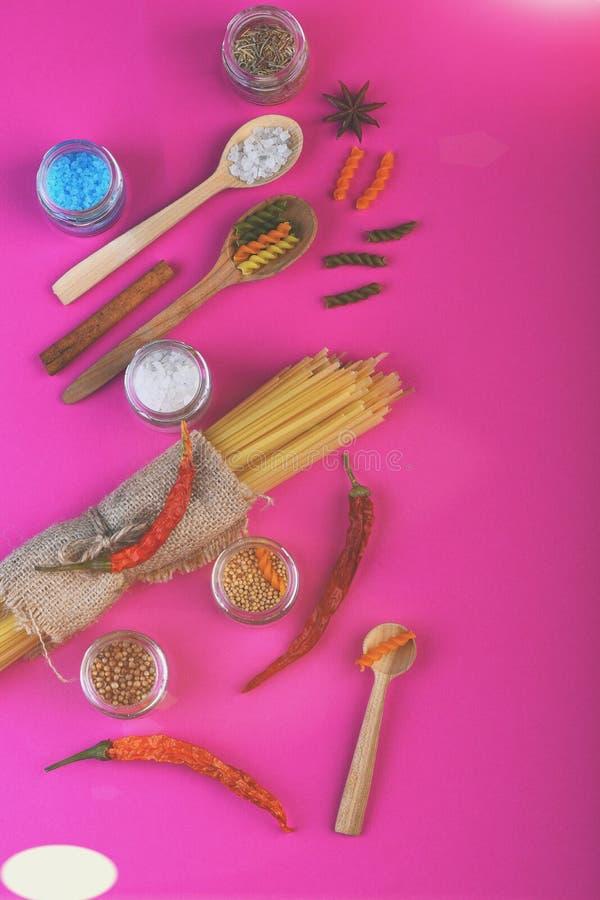 Mazzo di pasta secca degli spaghetti in tela di sacco con i cucchiai di legno fotografia stock