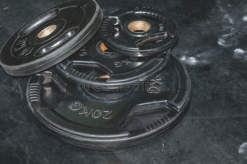 Mazzo di piatti neri pesanti del peso del bilanciere sul pavimento della palestra per l'immagine scura di forte contrasto di alle immagine stock