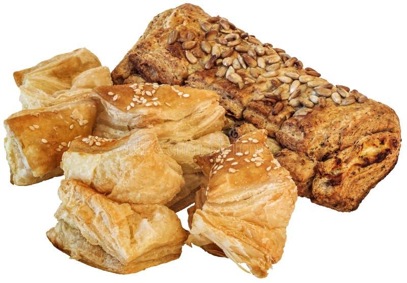 Mazzo di piccola pasta sfoglia quadrata del sesamo Zu-Zu e di pagnotta integrale del pane con i semi di girasole isolati su fondo fotografie stock