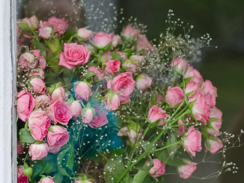 Mazzo di piccole rose rosa dietro il vetro fotografia stock libera da diritti