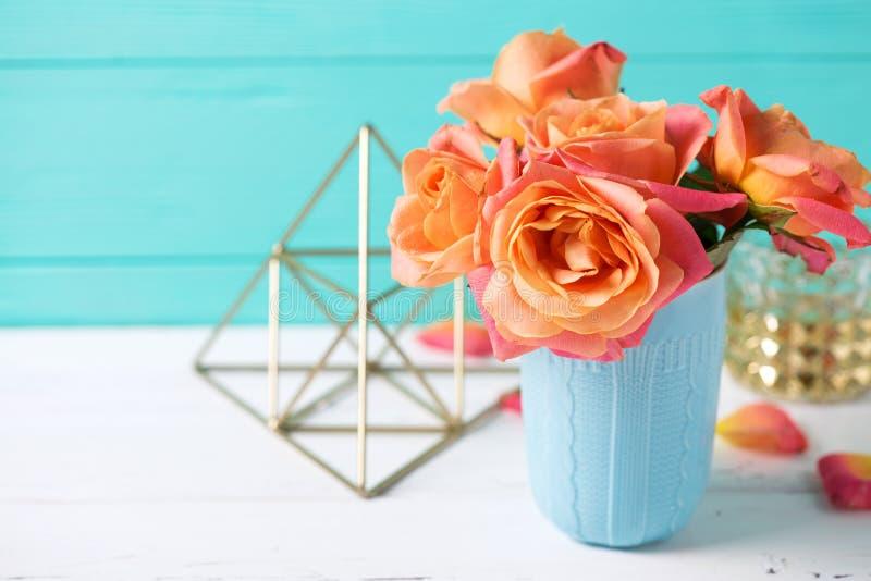 Mazzo di rose arancio fresche in tazza blu sul backgrou di legno bianco immagini stock