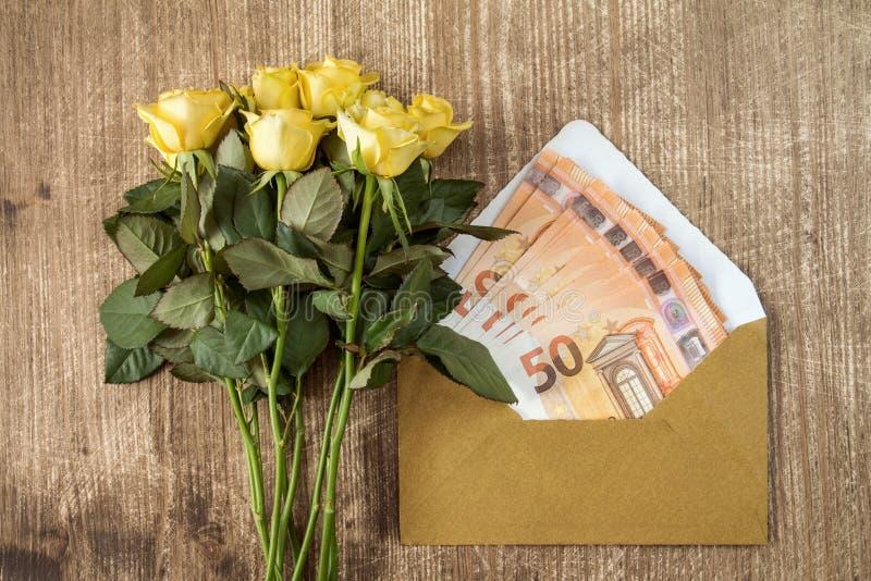 Mazzo di rose e di busta con soldi fotografie stock libere da diritti