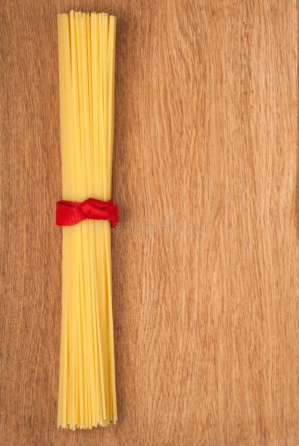 Mazzo di spaghetti legato in su con un nastro rosso fotografia stock libera da diritti