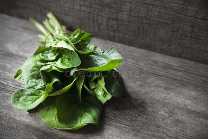 Mazzo di spinaci freschi avvolto con cordicella su vecchia superficie di legno fotografie stock