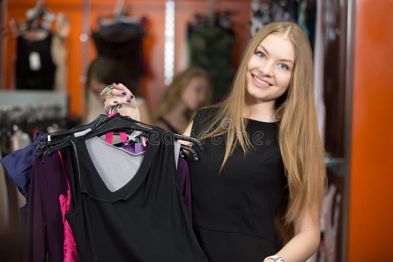 Mazzo di trasporto della donna attraente di indumenti in negozio immagini stock libere da diritti